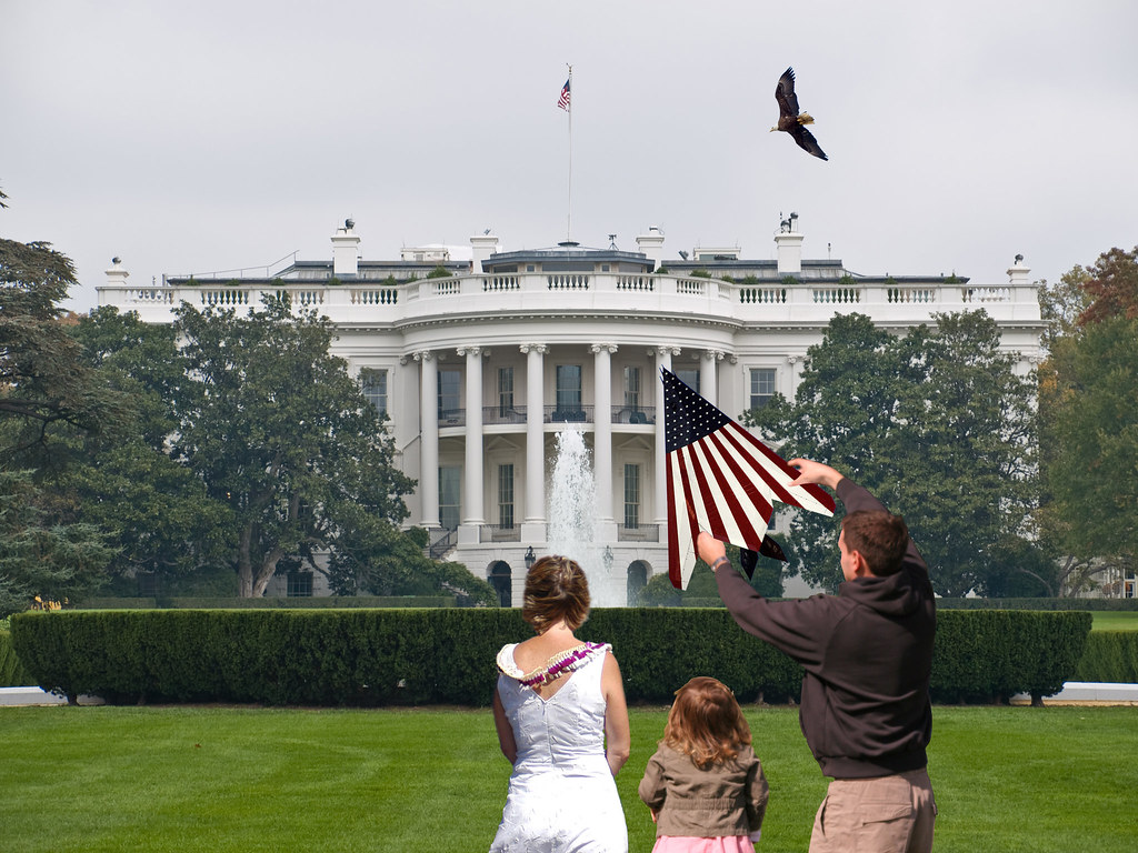 A father prepares to fly a kite on the front lawn of the White House